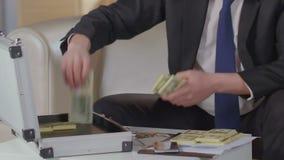 在衣服的男性打开手提箱采取一团美元在它外面,非法贿赂 股票录像