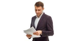 在衣服的英俊的商人与纸 免版税图库摄影