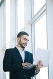 在衣服的英俊的商人与膝上型计算机 免版税库存图片