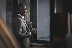 在衣服的非裔美国人的商人与杯威士忌酒抽烟的雪茄 免版税库存照片
