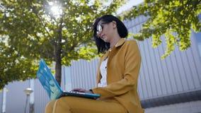 在衣服穿戴的太阳镜的美丽的女商人使用手提电脑在断裂期间户外,年轻女人坐 股票视频