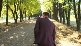 在衣服跳舞的成功的愉快的商人在秋天公园享受成功的 影视素材