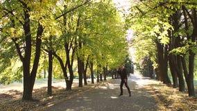 在衣服跳舞的成功的愉快的商人在秋天公园享受成功的 股票录像