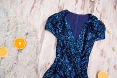 在衣服饰物之小金属片和桔子在一张灰色虚假毛皮,木背景的蓝色礼服 时兴的概念,顶视图 库存照片