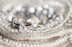 在衣服饰物之小金属片和珍珠的婚戒 免版税库存照片