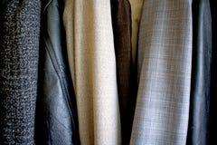 在衣橱安置的不同的衣裳 好纹理 免版税库存图片