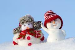 在衣物的两个雪人是下的 免版税库存照片