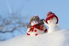 在衣物的两个雪人是下的 免版税库存图片