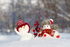 在衣物的两个雪人是下的 图库摄影