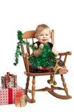 在补缀品礼服的逗人喜爱的圣诞节婴孩岩石 免版税库存图片