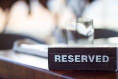在表上的后备的木卡片板材有模糊的背景 在餐馆的保留位子 - 休闲、浓缩的人们和的服务 免版税库存图片