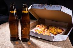 在表上的啤酒瓶由有开放盒盖的薄饼箱子 免版税库存照片
