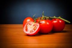 在表上的蕃茄在黑背景前面 免版税库存照片