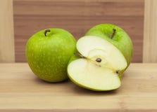 在表上的被对分的和整个绿色苹果 免版税图库摄影