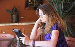 在表上读她的片剂的一名妇女 免版税库存照片