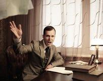 在表之后的恼怒的生意人 免版税库存照片