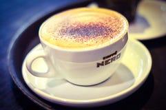 在表热奶咖啡安置的一杯在Caffe尼罗,英国 免版税库存图片