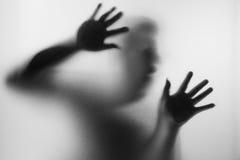 在表面无光泽的玻璃后的恐怖人在黑白 模糊的韩 库存照片