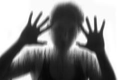 在表面无光泽的玻璃后的恐怖妇女,称呼黑白,模糊的手和身体 免版税库存图片