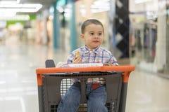在衬衣的一个愉快的孩子在一辆台车在购物中心坐并且吃面包 库存图片