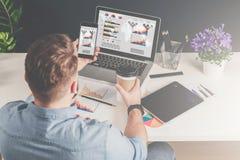 在衬衣的年轻商人在办公室坐在桌上并且使用有图、图和图表的智能手机在屏幕上 免版税图库摄影