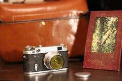 在袋子旁边的葡萄酒照相机照片设备和照片框架的 库存图片