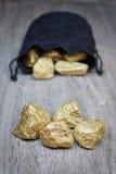 在袋子的块金分散的石头。 免版税库存照片