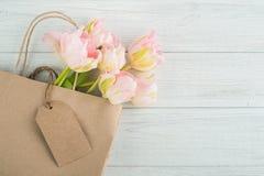 在袋子的桃红色春天郁金香与空白的标记 图库摄影