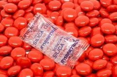 在袋子的矽土凝胶在红色糖涂上了药片片剂维生素 库存照片
