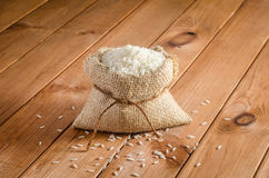 在袋子的米在一张木桌上 免版税库存图片
