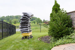 在袋子的腐土在庭院里堆了在一个推车的上流 免版税库存照片