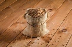 在袋子的荞麦在一张木桌上 免版税库存照片