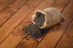 在袋装物质背景的黑胡椒豌豆 库存图片