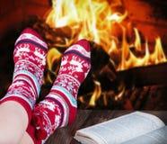 在袜子的圣诞节女性腿在灼烧的fi的背景 库存图片