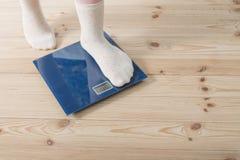 在袜子的女性脚在地板等级 库存图片