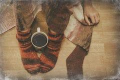 在袜子的女性腿与一个杯子coffe通过窗口冬天 库存图片