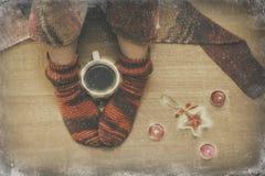 在袜子的女性腿与一个杯子coffe通过窗口冬天 免版税库存图片