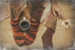在袜子的女性腿与一个杯子coffe通过窗口冬天 免版税图库摄影