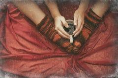在袜子的女性腿与一个杯子coffe通过窗口冬天 图库摄影