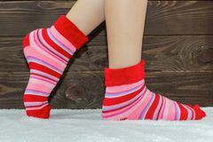 在袜子的妇女` s腿在地毯 木背景 温暖, stripey袜子 免版税库存照片