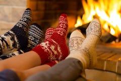 在袜子的家庭在冬天或圣诞节时间临近壁炉 免版税库存图片