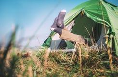 在袜子的旅客腿从野营的帐篷非常突出  库存照片