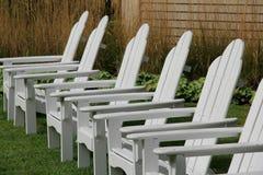 在被修剪的草坪的六把白色阿迪朗达克椅子 免版税库存照片