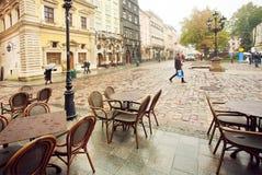 在被修补的街道上的冷的早晨有老镇的空的室外餐馆的 库存照片