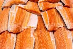 在被击碎的冰的新鲜的海鲜在鱼市上 在显示柜台的未加工的三文鱼内圆角在商店 鱼去骨切片的bacground 免版税库存图片