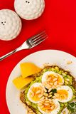 在被击碎的鲕梨的煮沸的鸡蛋与的松果和开放的黑麦面包 免版税图库摄影