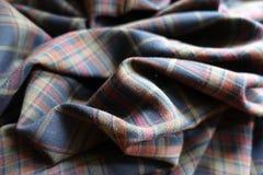 在被制服的颜色的被折叠的格子花呢披肩织品 免版税图库摄影