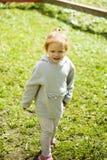 在被剪的绿草的小的愉快的红发女孩奔跑在宜人的太阳下的儿童公园 免版税库存照片