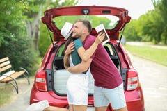 在被包装的汽车和手提箱附近的美好的年轻夫妇 免版税图库摄影