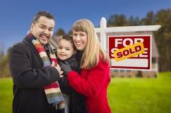 在被卖的房地产标志和议院前面的家庭 免版税库存照片